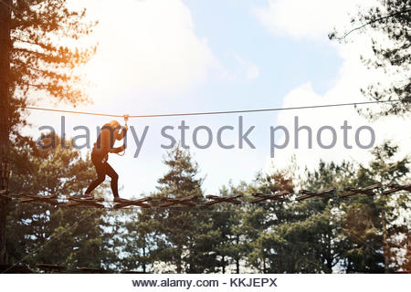 woman crossing high wire ropes - Stock Image