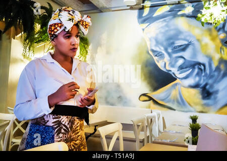 Cartagena Colombia Old Walled City Center centre Centro Aji Dulce restaurant waitress Hispanic resident residents woman employee typical head turban w - Stock Image