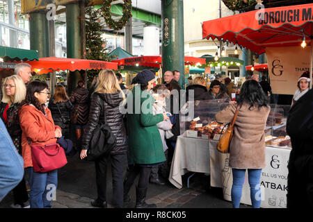 Crowd of people looking at food stalls inside Borough Market at Christmas time in Southwark, South London UK  KATHY DEWITT - Stock Image