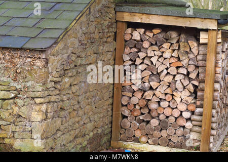 Log storage in garden of house in the north Oxfordshire village of Hook Norton - Stock Image