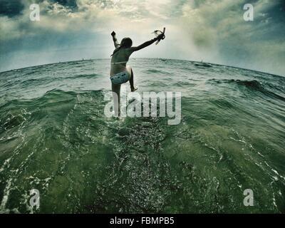 Girl Splashing Water In The Sea - Stock Image