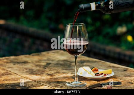 pouring red wine at the table - Stock Image