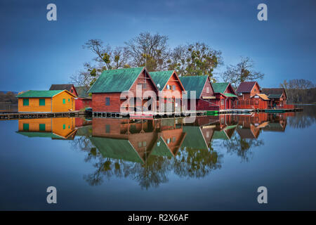 Tata, Hungary - Wooden fishing cottages on a small island at lake Derito (Derito to) at blue hour with reflection - Stock Image