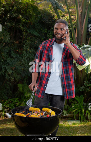 Man talking on a cellphone and barbecuing food - Stock Image