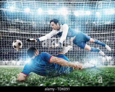 Goalkeeper catches the ball in the stadium during a football game. - Stock Image