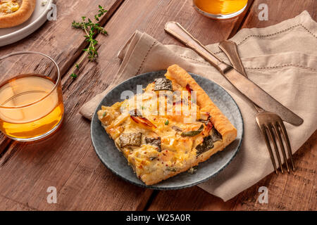 Slices of a zucchini and goat cheese pie with thyme on a dark rustic wooden background with white wine - Stock Image