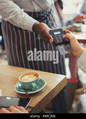 Customer paying waiter with credit card reader at cafe table - Stock Image