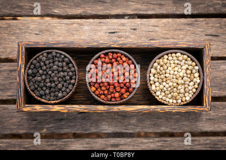 Organic kampot white red and black pepper corns in natural rustic style wood display in cambodia - Stock Image