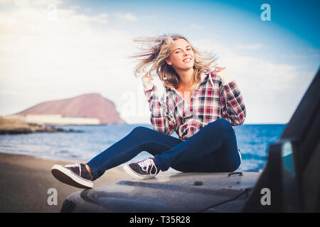 Playful young attractive blonde play with the wind sitting on his car and enjoying the travel alternative adventure vacation alone - hipster woman peo - Stock Image