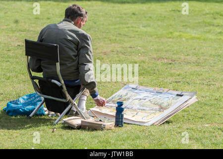London, UK. 10th August, 2017. a man works on a painting of Kensington Gardens as warm weather returns in London, UK. Credit: Ben Furst/Alamy Live News. - Stock Image