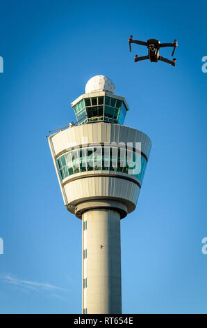 Digital composite of drone and air traffic control tower at airport. - Stock Image