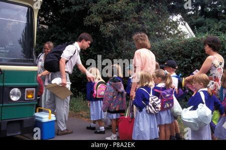primary school children boarding bus to go on school trip - Stock Image
