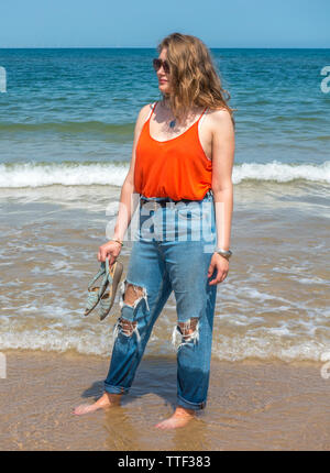 Beautiful young woman, with long wavy hair, wearing ripped jeans and holding shoes, standing bare footed in the surf on a hot summer day in England. - Stock Image