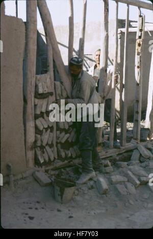 Man in a Muslim cap building a wall of brick and mortar; Bukhara Uzbekistan. - Stock Image