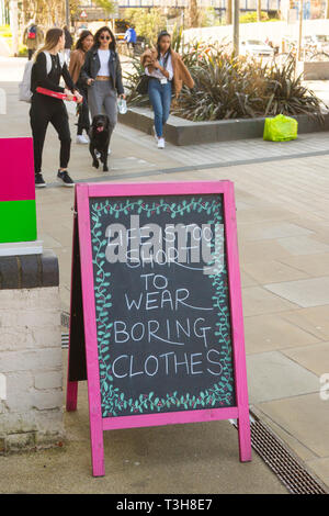 A hand-drawn shop sign in chalk saying 'Life is too short to wear boring clothing' - Stock Image