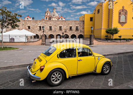 A yellow Volkswagen battle passes the Aranzazu Chapel and San Francisco Convent in the Plaza de Aranzazu in the state capital of San Luis Potosi, Mexico. The chapel and convent was built between 1749 and 1760 and features Churrigueresque details and tiled domes. - Stock Image