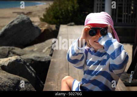 Little girl looks through binoculars. - Stock Image