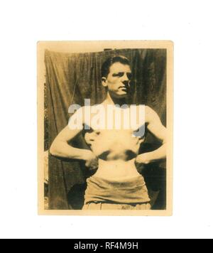 Vintage black and white photo of bare chested man doing a body building pose 1940s to 1950s military - Social History - Stock Image