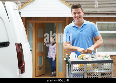Portrait Of Driver Delivering Online Grocery Order To House - Stock Image