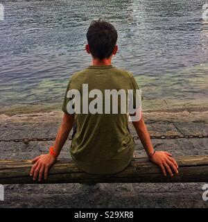 Rear view of young athlete looking at river - Stock Image
