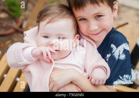 Elementary school age Caucasian child boy holding tenderly his beloved little sister girl somewhere outside. Brother to sister sincere love concept - Stock Image