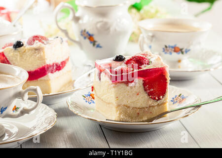 Portions of cheesecake with strawberries, blueberry and jelly served with cup of coffee - Stock Image