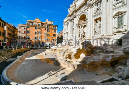 An art restorer cleans and maintains the empty, drained Trevi Fountain on a sunny afternoon in early autumn in Rome, Italy - Stock Image