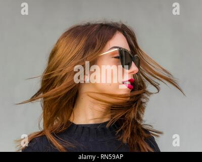 Pretty teen girl blonde hair portrait blowing wind with sunglasses looking away aside smiling - Stock Image