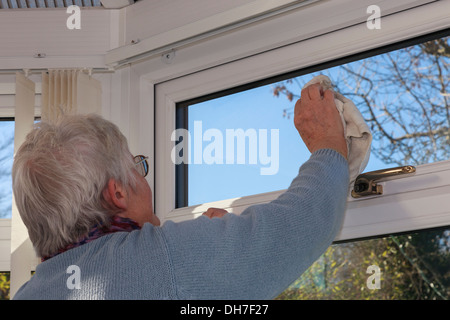 Elderly retired woman cleaning windows with a hand cloth inside a house conservatory. UK, Britain - Stock Image