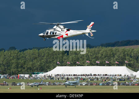 Chichester, West Sussex, UK. 13th Sep, 2013. Goodwood Revival. Goodwood Racing Circuit, West Sussex - Friday 13th September. A helicopter lands at the in-field aerodrome under dark skies. Helicopters are often used to transport VIP guests into the event. © MeonStock/Alamy Live News - Stock Image