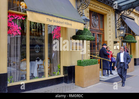 A man walks past the entrance to the Waldorf Hilton hotel in London, which dates back to 1908 and was originally known as The Waldorf Hotel - Stock Image