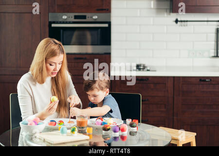 happy blonde mother and four-year old son making homemade Easter eggs, enjoying leisure time spent together at home. Family celebrating Easter. Parent - Stock Image