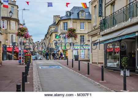 The long, one way Rue Saint-Jean, the main street full of cafes and shops in the Normandy city of Bayeux, France - Stock Image