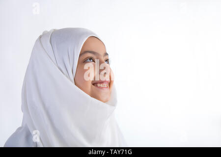 Young Muslim girl wearing hijab looking away and smiling - Stock Image