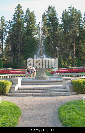 3 teen girls take their picture by the Davenport Fountain, Duncan Garden, Manito Park, Spokane, Washington State, USA. - Stock Image