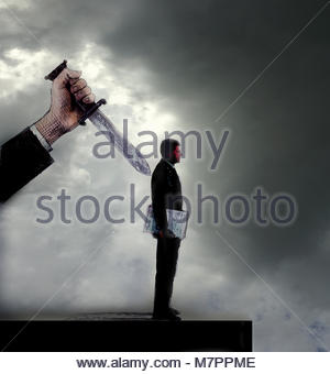 Businessman being stabbed in the back - Stock Image
