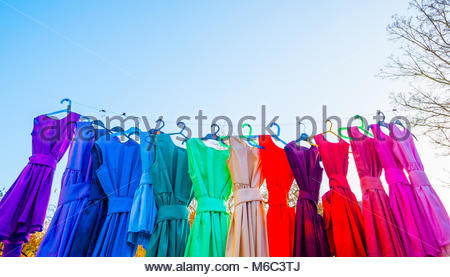 Children's Colourful dance dresses on a washing line in the late afternoon winter sun. 14 Rainbow coloured hand - Stock Image