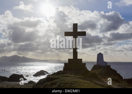 Stone cross and old lighthouse (Twr Mawr) in silhouette against sunshine on Ynys Llanddwyn Island, Newborough, Isle of Anglesey, North Wales, UK - Stock Image