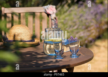 Antique blue glass water jug and two glasses in a summer garden on a sunny day. - Stock Image