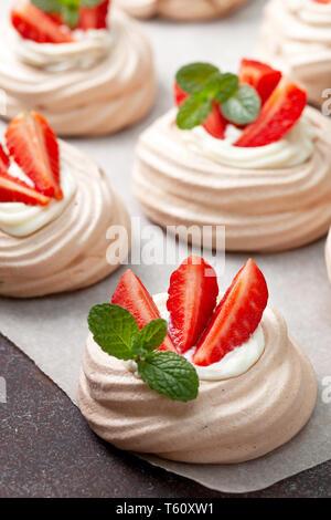 pavlova chocolate mini cakes with strawberries close-up - Stock Image