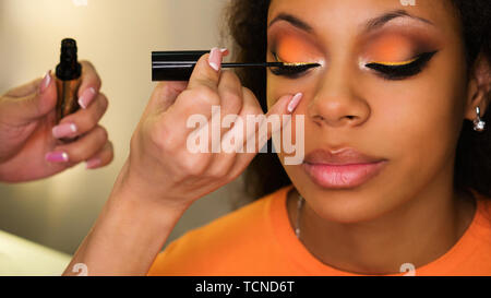Makeup artist applies mascara to eyelashes of african girl. Evening make-up. Closeup portrait. Fashion photo - Stock Image