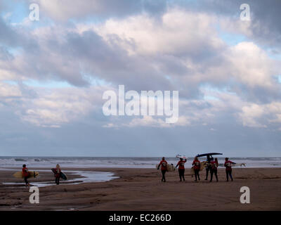 Surf school heading for the sea on a winter's day, Bude, Cornwall, UK - Stock Image