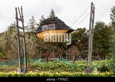 The Flying Mud Boat is a  mysterious building with trees protruding from the roof. The four protruding wooden pillars are made of locally-made trees,  - Stock Image