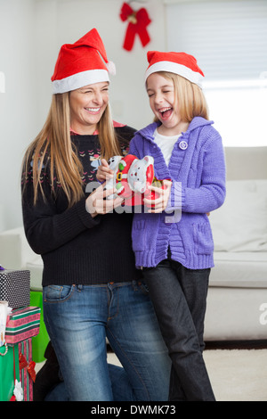 Cheerful Daughter And Mother With Christmas Present - Stock Image