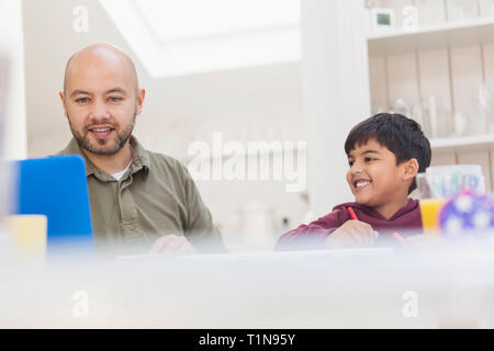 Father and son using laptop and coloring at table - Stock Image