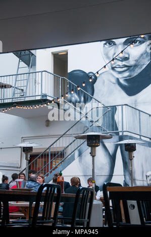Diners seated beneath a Muhammad Ali mural in Fish Lane, South Brisbane, Queensland, Australia - Stock Image