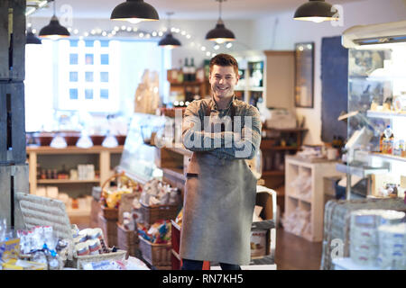 Portrait Of Smiling Male Owner Of Delicatessen Shop Wearing Apron - Stock Image