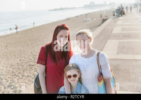 Portrait smiling lesbian couple and daughter on sunny beach boardwalk - Stock Image