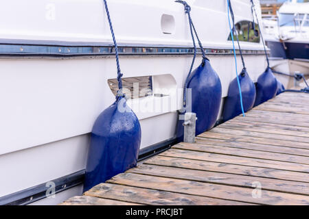 Buffer fenders bumpers on the side of a pleasure boat at a marina pontoon. - Stock Image