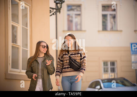 Two happy young women walking on the streets. Mid shot - Stock Image